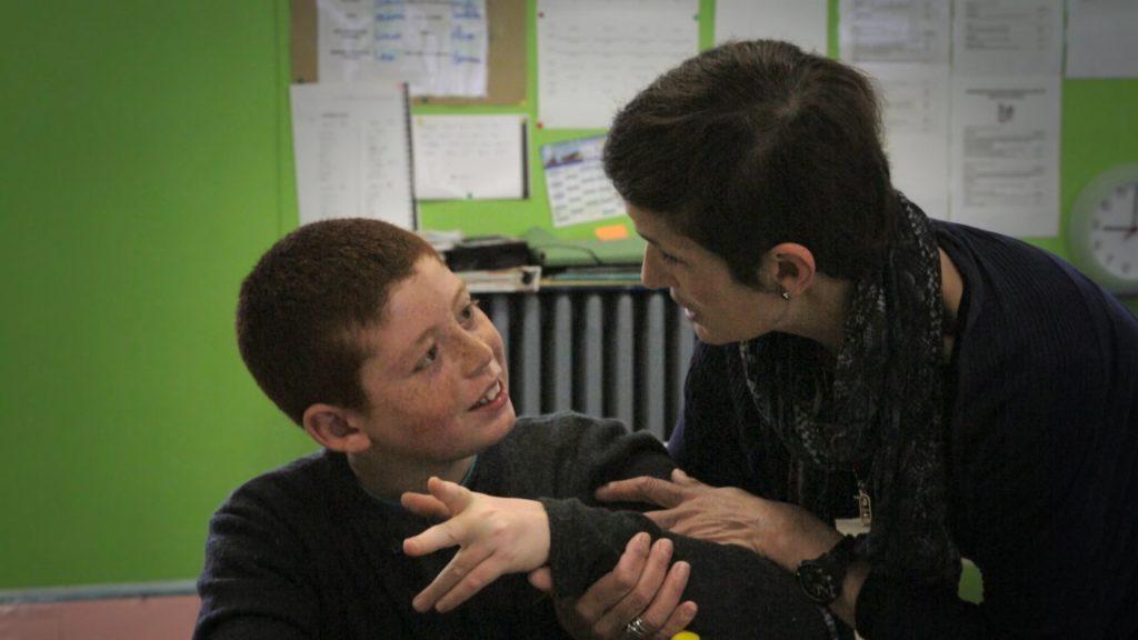 une enseignante regarde un élève d'une classe CLIS, avec une distance juste.