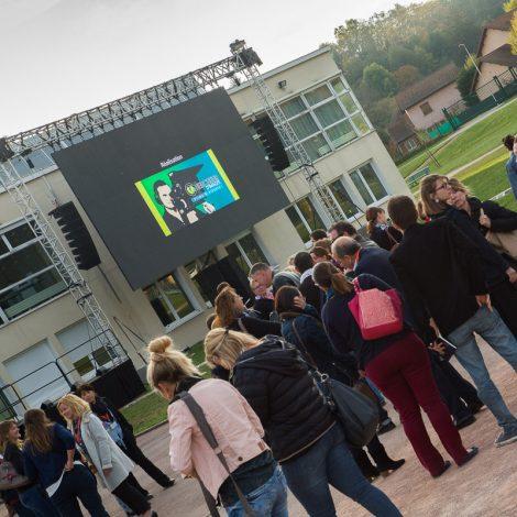 foule se pressant devant un écran géant sur lequel apparait le logo de Chercheur d'images, prestataire savoyard en audiovisuel.