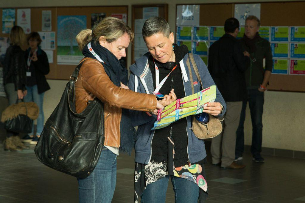 deux personnes regardent le plan de la journée du Festival de la relation, conçu par Chercheur d'images, et pointent du doigt le lieu où elles vont se rendre.