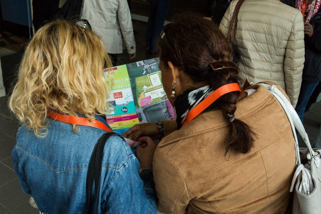 deux personnes regardent le plan de la journée du Festival de la relation, conçu par Chercheur d'images, pour se situer.